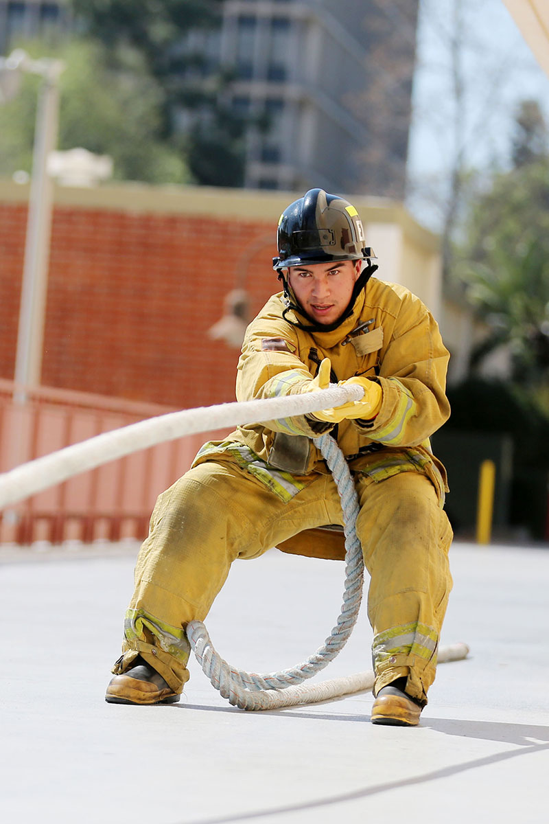 Student fireman pulling a rope