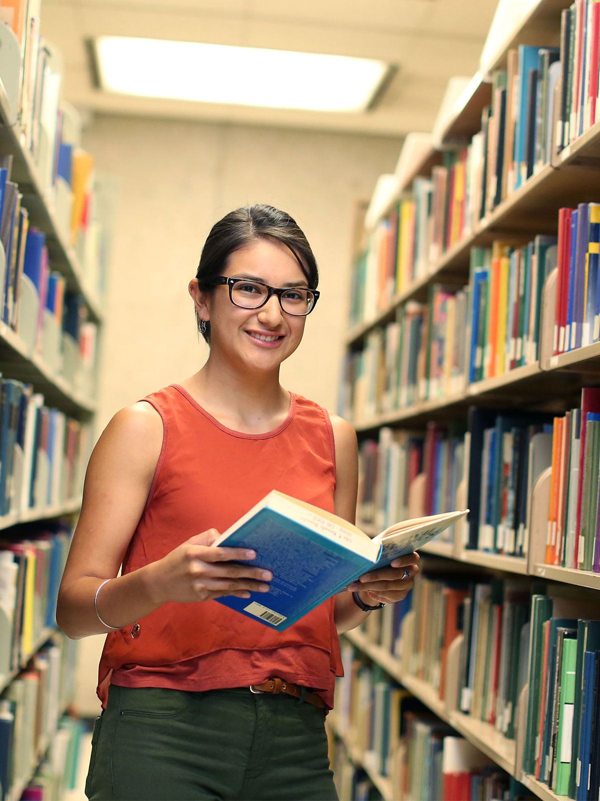 Student holding a book in library